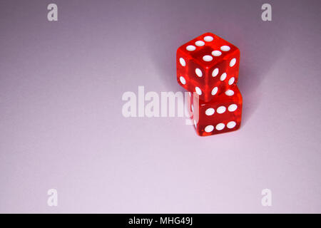 Stacked red luminescent casino gambling dice - vibrant colors on gray background - Stock Photo