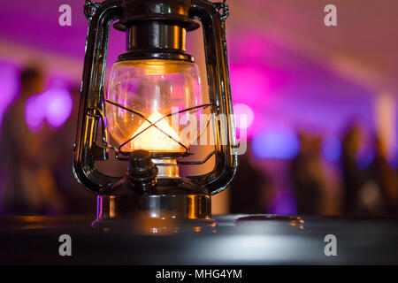 Group of unrecognizable young people dancing during a party with a traditional lantern in the foreground - Stock Photo