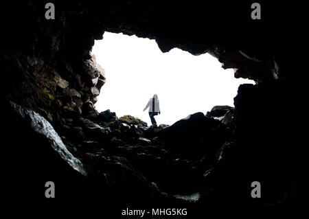 Silhouette of woman hiking along mouth of cave - Stock Photo