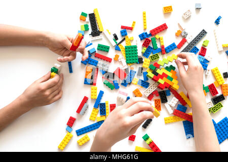 Children hands play with colorful lego blocks on white table.