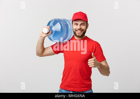 Portrait smiling bottled water delivery courier in red t-shirt and cap carrying tank of fresh drink and showing thumb up isolated over white background - Stock Photo