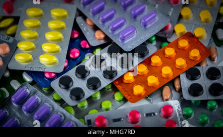 Pile of Colorful tablets pill in blister packaging. Pharmaceutical industry concept. Pharmacy drugstore. Pain killer and drug interaction with charcoa - Stock Photo
