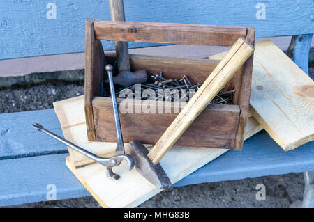 Vintage Toolbox with tools. Old wooden box with building tools, boards for repair on a wooden bench. Carpenter toolbox. Old working tools. - Stock Photo