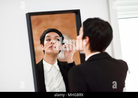 Young woman with very short haircut, putting makeup on in front of the mirror at home. Girl wearing suit with black blazer jacket. - Stock Photo