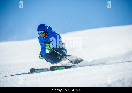 A male skier carving turns on a piste in the French alpine resort of Courchevel. - Stock Photo