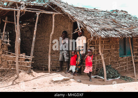 A poor African family composed of three children and their mother, put out of their hut made of excrement and cement on the borders of the Savannah - Stock Photo