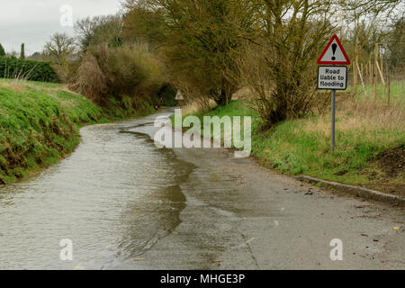 Flooded road after heavy rain with sign 'road liable to flooding' in England - Stock Photo