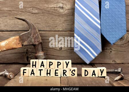 Happy Fathers Day wooden blocks with tools and ties in the background against rustic wood - Stock Photo