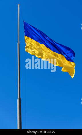 large textile lag of Ukraine develops in the wind against the background of a blue clear sky - Stock Photo