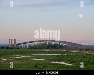 Isle of Sheppey, Kent, UK. 1st May, 2018. UK Weather: the full moon sets over the Isle of Sheppey crossing at sunrise as commuters head to work. Credit: James Bell/Alamy Live News - Stock Photo