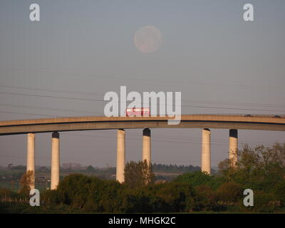 Isle of Sheppey, Kent, UK. 1st May, 2018. UK Weather: the full moon sets over the Sheppey Crossing as the sun rises and commuters head to work.  Credit: James Bell/Alamy Live News - Stock Photo