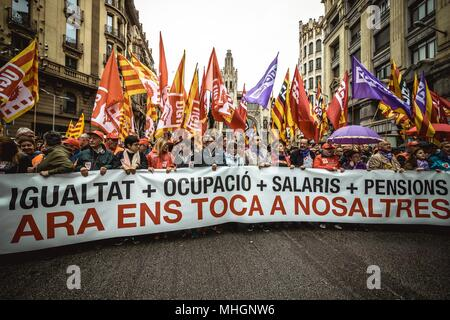 Barcelona, Spain. 1 May, 2018:  Thousands of demonstrators with their waving flags march behind their banner during a manifestation organized by the mayor unions CC.OO and UGT, to protest for more equality, occupation, wage and pensions under the slogan 'now is our turn' on 1st of May. - Stock Photo