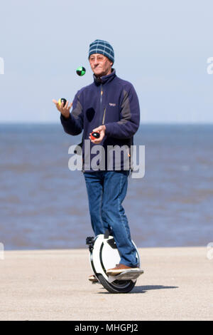 Blackpool Seafront, 1st May 2018. UK Weather.  A lovely sunny but cold & breezy day over the north west of England as a man juggles whilst riding his EUC or electric uni-cycle along the promenade to take in the seaside on Blackpool seafront in Lancashire.  Credit: Cernan Elias/Alamy Live News Stock Photo