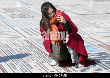 Blackpool Lancashire. 1st May, 2018. UK Weather:  Sunny start to the day on the Fylde Coast. Foreign tourists enjoy the attractions on the seafront promenade.  The comedy carpet or pavement provides a comic backdrop for photographers intent on taking selfies as they bend, stretch and contort their bodies into unnatural positions to capture the perfect shot. MediaWorldImages/AlamyLiveNews. Stock Photo