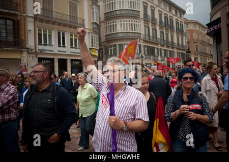Malaga, Spain. 1st May, 2018. A protester with a sticker of union CCOO raises his fist as he takes part in a demonstration during the May Day rally or Labour Day in Malaga. Thousands of people called by the General Workers Union (UGT), and the labour union 'Comisiones Obreras' (CCOO), protest today in Malaga during a nationwide demonstration in favor of workers rights and decent employments under the main slogan. ''Its time to win' Credit: Jesus Merida/SOPA Images/ZUMA Wire/Alamy Live News - Stock Photo