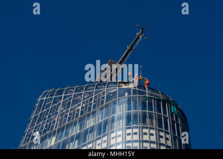 London, UK. 1st May, 2018. Workers take advantage of the clear calm weather in central London to work on the outside of the new apartment block at number 1 Blackfriars in central London. Clear blue skies over the capital city enable construction workers or riggers to work on the outside of a very tall new building at number one Blackfriars. Serious head for heights as workers hang from the outside and top of a new block of apartments in central London. Credit: Steve Hawkins Photography/Alamy Live News - Stock Photo