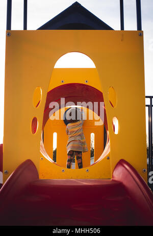 A faceless young girl plays at a playground on a sunny afternoon. - Stock Photo