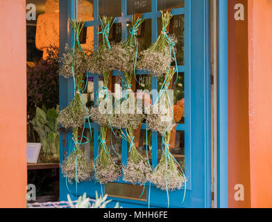 Bouquet of dried flowers hanging on the blue door - Stock Photo