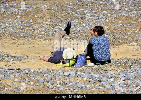 Middle aged couple relaxing on the pebble beach in Cromer Norfolk England UK - Stock Photo