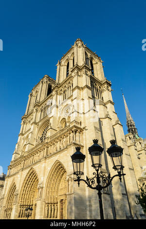 The facade and bell towers of Notre-Dame de Paris cathedral, showing the three portals and rose window with a vintage street light in the foreground. - Stock Photo
