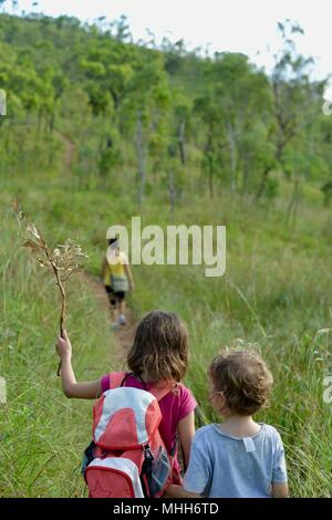 Mother and children walking through long grass through a forest in an inspiring scene, Mount Stuart hiking trails, Townsville, Queensland, Australia - Stock Photo