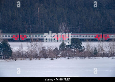 City electric train on the background of a snowy landscape - Stock Photo