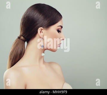 Attractive Young Woman with Makeup, Healthy Ponytail Hairstyle and Earrings with Pearls - Stock Photo