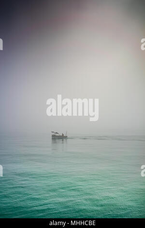 Small fishing boat in the mist off Worthing seafront in Springtime - Stock Photo