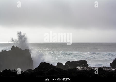 Waves crashing against black volcanic rock formations - Stock Photo