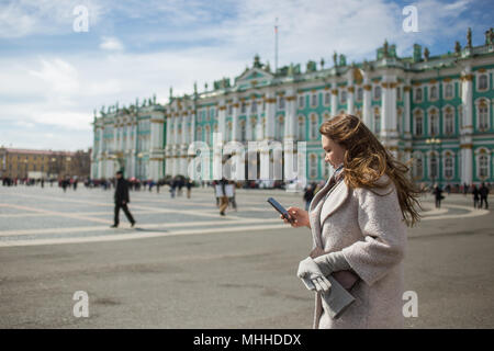 Young traveler woman wearing casual classic coat, holding cellphone, using app, gps, searching for direction while walking in Saint-Petersburg, Palace Square, Winter Palace in spring or autumn time. - Stock Photo