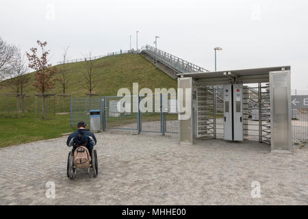 A man in a wheelchair looking up at visitor hill he cannot access in the Visitors Park at Munich Airport, Munich, Germany. - Stock Photo