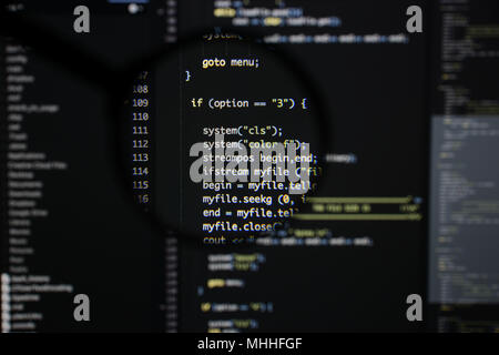 Real c / c++ code developing screen. Programing workflow abstract algorithm concept. Lines of c / c++ code visible under magnifying lens. - Stock Photo