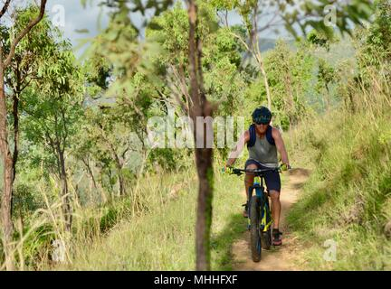 Male bicycle rider on a mountain bike going down a hill on a gravel track,  Mount Stuart hiking trails, Townsville, Queensland, Australia - Stock Photo