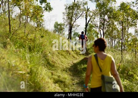 Lady walking on path with mountain bike in distance, Mount Stuart hiking trails, Townsville, Queensland, Australia - Stock Photo