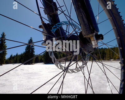 Cycling on large tyres in fresh snow. Biker goes by bike on the snowy road in the mountains. Picture taken in HDR mode. - Stock Photo