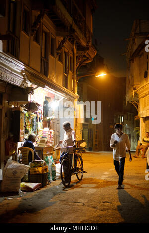 Man on the phone in front of a tuk tuk. Shopping street in the crowded streets in the old city of Ahmedabad, Manek Chowk. - Stock Photo