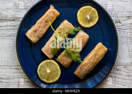 Turkish Lahana Sarmasi / Cabbage Rolls in a dark blue plate. - Stock Photo