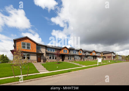 Row of brand new townhomes for sale in North America suburban neighborhood - Stock Photo