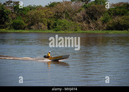A villager travelling along the River Amazon near Manaus in a motor boat. - Stock Photo