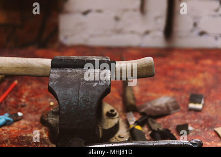 Wooden handle with leather winding is fixed in vice in carpentry workshop. Tool for manual labor - Stock Photo