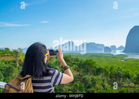 Young traveler woman backpacker use mobile phone take a photo of beautiful of sunrise nature at top of mountain view,Freedom wanderlust concept,Khao S - Stock Photo