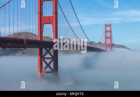 Thick low fog formed under the Golden Gate Bridge in San Francisco, California, United States, on an early spring morning. - Stock Photo