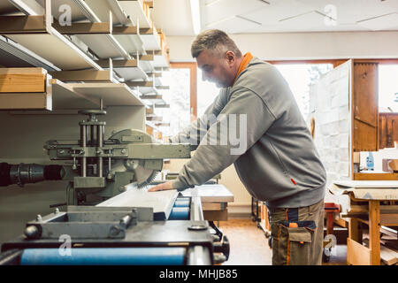 Tinner working on metal sheets in his workshop - Stock Photo