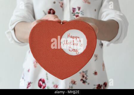 Front view of womans hands holding heart box gift for Mother's day. Gratefulness present concept - Stock Photo