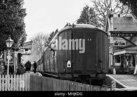 Black & white nostalgia. Rear view of vintage railway carriage pulled by steam engine waiting at SVR Hampton Loade station. Guard waves from window. - Stock Photo