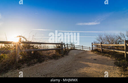 Wooden fence leads to beach near lighthouse in Cape May, NJ, on a sunny morning - Stock Photo