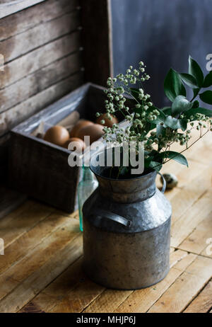 Rustic bouquet of herbs in aluminum cans, chicken eggs in box on the table
