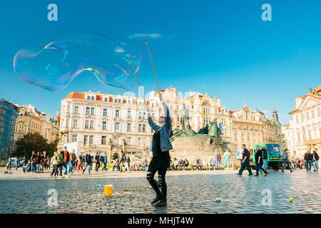 PRAGUE, CZECH REPUBLIC - OCTOBER 15, 2014: Unidentified young woman makes soap bubbles in Old Town Square (Staromestske namesti) in Prague, Czech Repu - Stock Photo