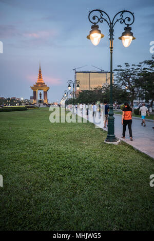 Statue and monument of King Father Norodom Sihanouk illuminated at twilight in distance. Phnom Penh Cambodia, South East Asia - Stock Photo