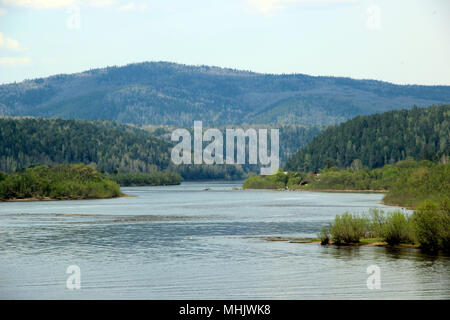 Amazing landscape of the winding river and wooden mountain ahead. Several roofs and fishermen far away on the right shore - Stock Photo